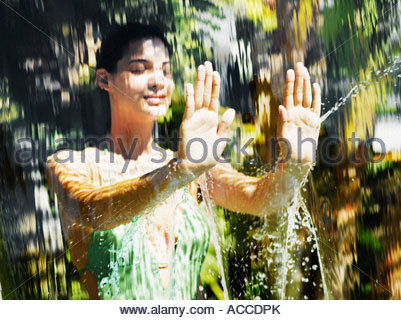 Woman in a bathing suit behind a waterfall - Stock Photo