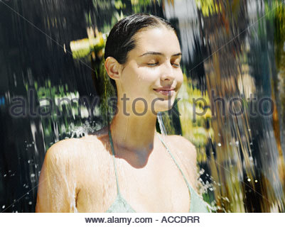 Woman in a bathing suit walking through a waterfall - Stock Photo