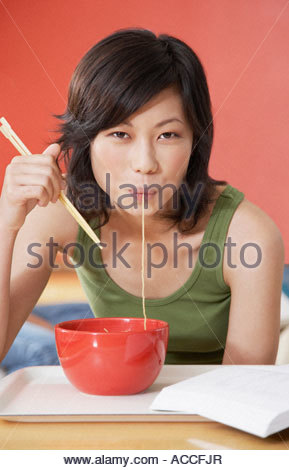 Young Woman eating bowl of noodles with chopsticks in cafeteria - Stockfoto