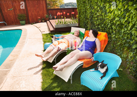 Couple relaxing on lawn chairs in backyard - Stock Photo
