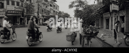 Asia Vietnam Hanoi Woman sells roses from her the back of her bicycle while walking through crowded streets of Old - Stock Photo