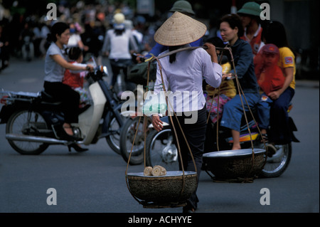 Asia Vietnam Hanoi Woman carries traditional baskets through chaotic traffic in citys Old Quarter - Stock Photo