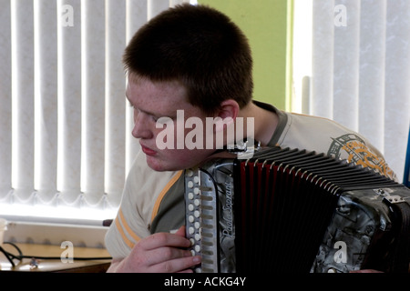 Closeup of a teenage boy practicing accordion in Ireland - Stock Photo