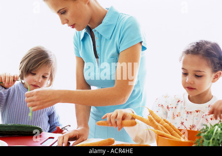 Mother and two children preparing meal in kitchen - Stock Photo