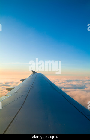 Airplane Wing At Sunset With Clouds - Stock Photo