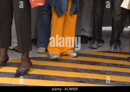 legs and feet of people waiting for a vapporetto water bus at a stop in Venice Italy with yellow safety stripes - Stock Photo