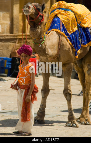 Vertical portrait of an ornately dressed young Indian boy and his camel waiting to give rides to tourists. - Stock Photo