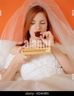 A bride sitting on a bed eating a box of chocolates - Stock Photo