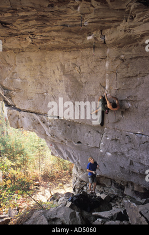 Male rock climber ascending overhanging cliff - Stock Photo