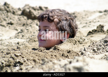 Little boy burried in the sand on a summers day - Stock Photo