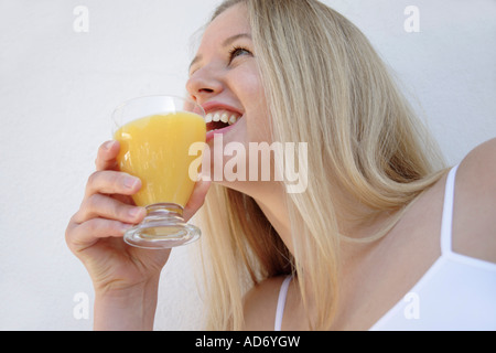 Young blond woman holding glass of orange juice, view from below - Stock Photo