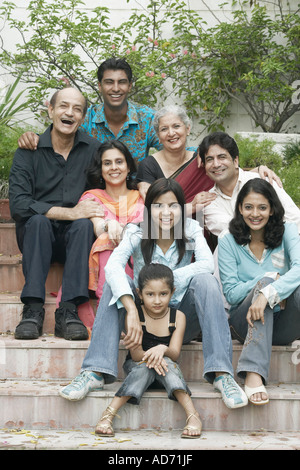 Portrait of a family sitting together on steps - Stock Photo
