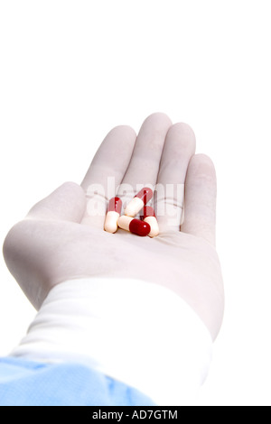 Doctor gloved hand holding medicine - Stock Photo