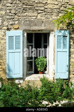 Blue shutters on the window of a traditional Provençal stone house, France - Stock Photo