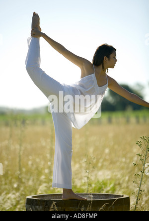 Woman doing yoga pose in field - Stock Photo