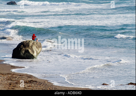 Ocean watch. A young man sits on a boulder by the pacific ocean in Carpinteria, California - Stock Photo