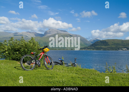 dh  CORPACH INVERNESSSHIRE Two mountain bikes parked by Loch Linnhe Ben Nevis mountain - Stock Photo