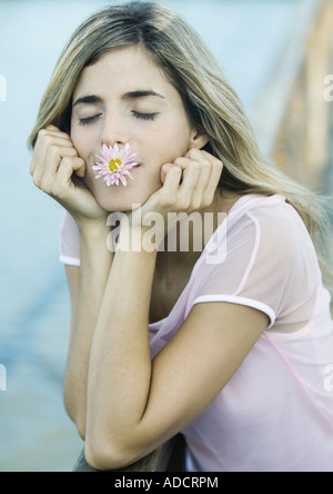 Woman with flower in mouth, eyes closed - Stock Photo