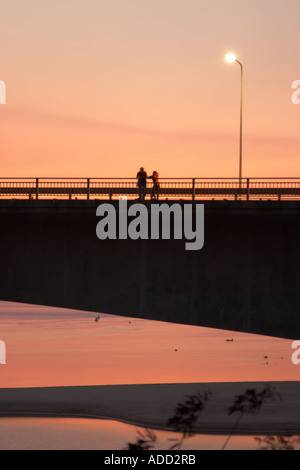 Two People Standing On Lao Japanese Bridge Across Mekong River At Sunset - Stock Photo