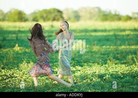Young hippie women dancing in field - Stock Photo