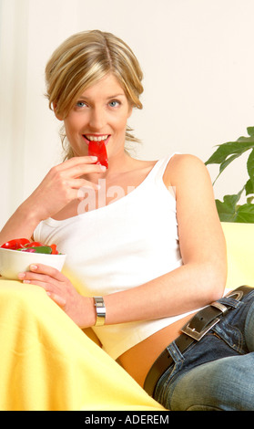 Woman on sofa eating red pepper - Stockfoto