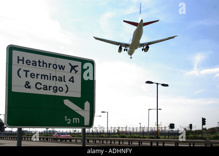 Heathrow Airport road direction sign for terminal 4 cargo area jet aircraft making landing approach low over dual - Stock Photo