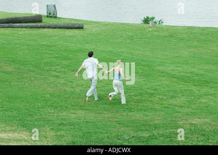 Couple running across grass, hand in hand, full length, high angle view - Stock Photo