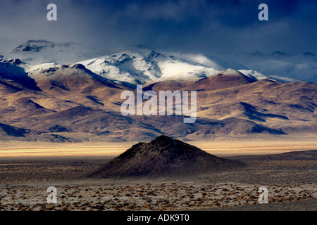 Small cinder cone and snow covered mountains Black Rock Desert National Conservation Area Nevada - Stock Photo