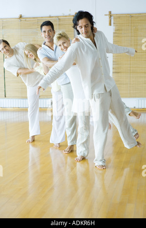 Group therapy, adults standing in line with one leg up, holding onto each other's shoulders - Stock Photo