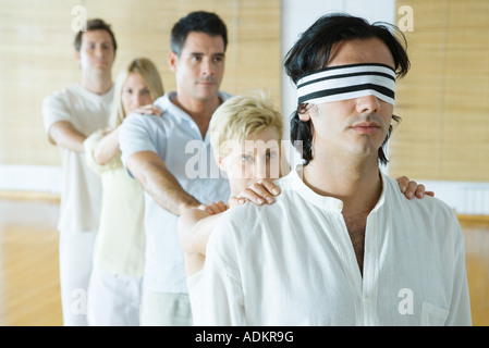 Group therapy, standing in single file line with hands on each other's shoulders, man in lead blindfolded - Stock Photo