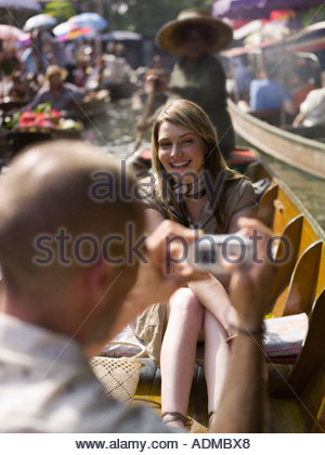 Man taking picture of girlfriend in row boat - Stock Photo
