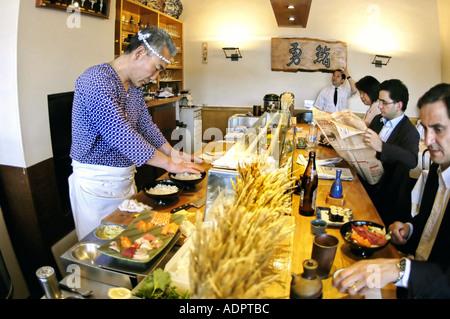 PARIS France, Interior 'Japanese Restaurant' 'Sushi Chef' preparing Meals in 'Isami' Businessmen LUNCH 'eating sushi' - Stock Photo