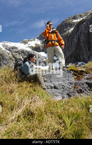 Man using walkie-talkie while a woman rests on rock on hiking trail in mountains - Stock Photo