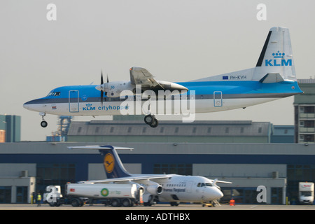 KLM Cityhopper regional aircraft landing and Lufthansa jet in the background at London City Airport England UK - Stock Photo