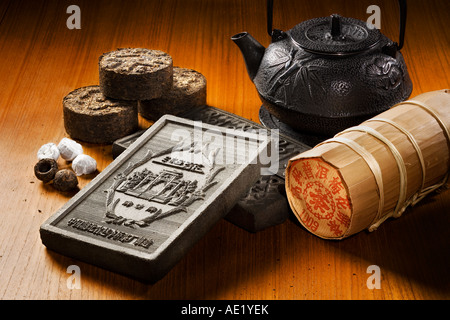A tea kettle, tea bricks and tea rolls wrapped in fancy packaging placed on a table top. - Stock Photo