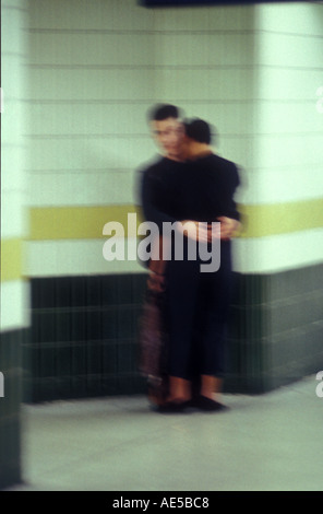 Hugging couple in an urban railway station sydney australia 1609 - Stock Photo