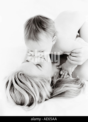 Mom and baby kissing on bed - Stockfoto