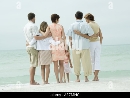 Group standing near edge of water on beach, rear view - Stock Photo