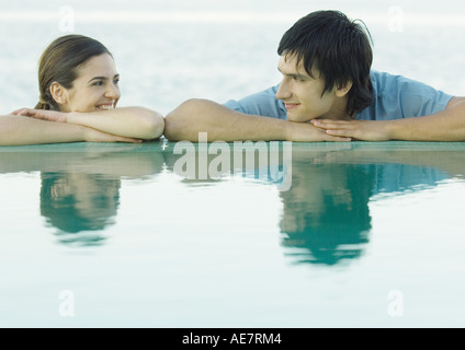 Young couple smiling at each other by water - Stock Photo