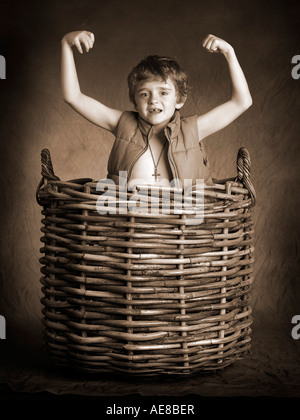 boy wearing cross and gilet popping out of large wicker basket - Stock Photo