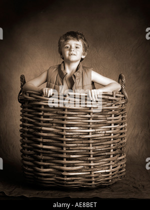 boy wearing cross and gillet popping out of large wicker basket - Stock Photo