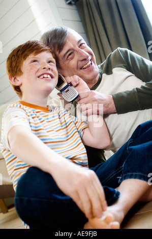Smiling senior man and boy using a mobile phone - Stock Photo