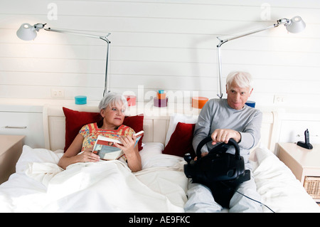Senior couple in bed, woman reading, man playing video game - Stock Photo