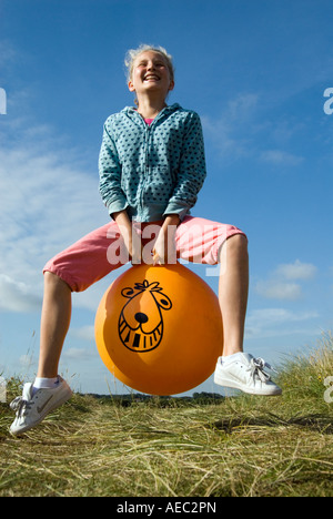 Young girl bouncing on a Space Hopper England UK - Stockfoto