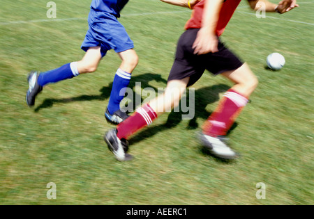 two football players running after the ball - Stock Photo