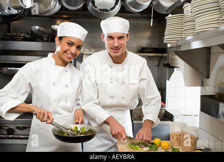 Male and female chefs in restaurant kitchen - Stock Photo