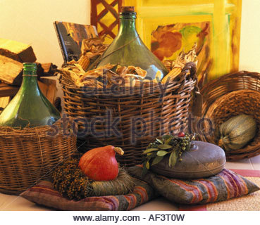 Pumpkin & hot-water bottle on cushions in front of 2 demijohns - Stockfoto
