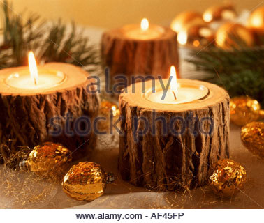 burning tea lights in tree stumps as christmas decorations stock photo