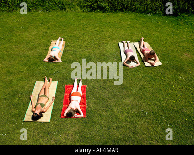 Young people sunbathing in a garden - Stock Photo