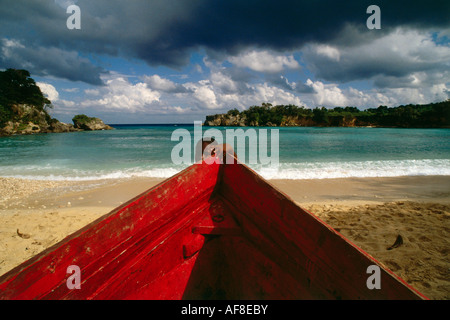 Boy and red boat on Boston Beach, Dragon Bay, Province of Portland, Jamaica, Caribbean - Stock Photo